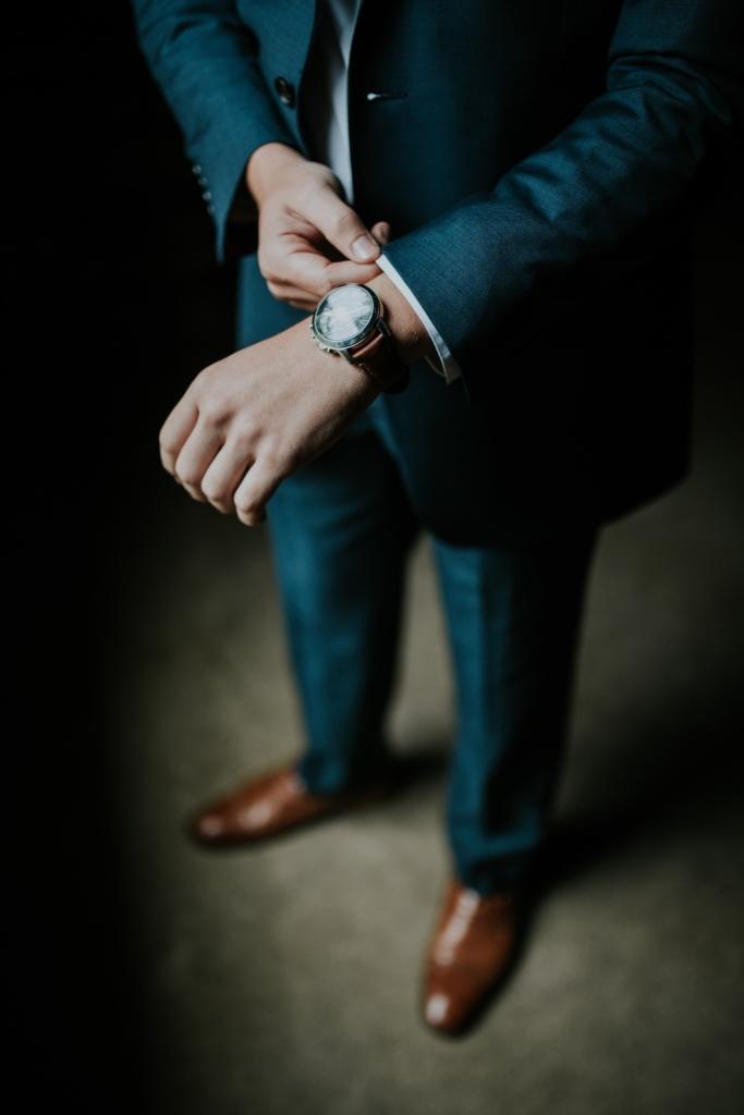 успешный бизнесмен в костюме с дорогими часами